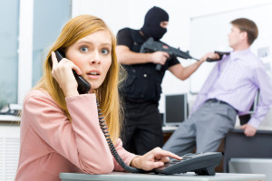 Portrait of horrified businesswoman pushing buttons of telephone while terrorist threatening her colleague at background